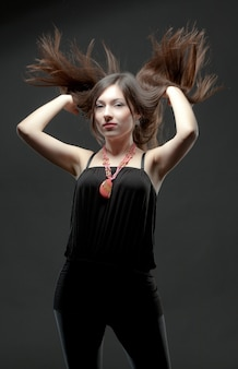 Young brunette woman in black casual clothing and massive accessories standing and turning head with wind in her hair over grey background in photo studio