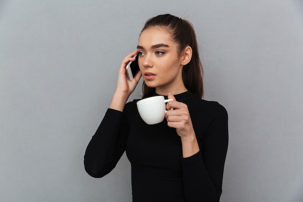Young brunette woman in black clothes talking by smartphone