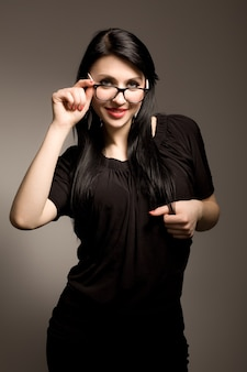 Young brunette woman in black clothing and glasses looking and smiling over white background in photo studio