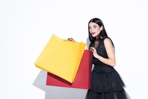 Young brunette woman in black dress shopping on white wall. attractive caucasian female model.