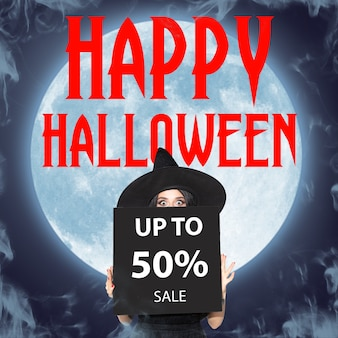 Young brunette woman in black hat. attractive female model against big moon midnight. calling for sale. black friday, cyber monday, sales, autumn concept. flyer for ad. up to 50 percents.