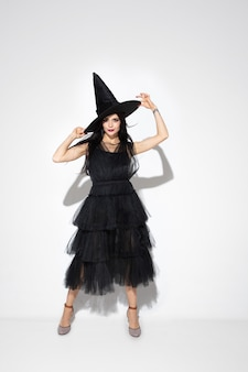 Young brunette woman in black hat and costume on white background. attractive caucasian female model. halloween, black friday, cyber monday, sales, autumn concept. copyspace. dancing, posing.