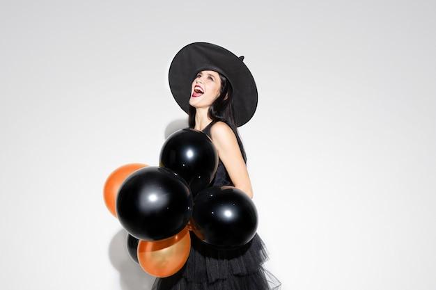 Giovane donna bruna in cappello nero e costume su sfondo bianco. modello femminile caucasico attraente. halloween, venerdì nero, cyber lunedì, vendite, concetto di autunno. copyspace. tiene palloncini, spaventoso.
