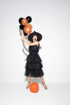 Giovane donna bruna in cappello nero e costume su sfondo bianco. modello femminile caucasico attraente. halloween, venerdì nero, cyber lunedì, vendite, concetto di autunno. copyspace. tiene i palloncini, scioccato.