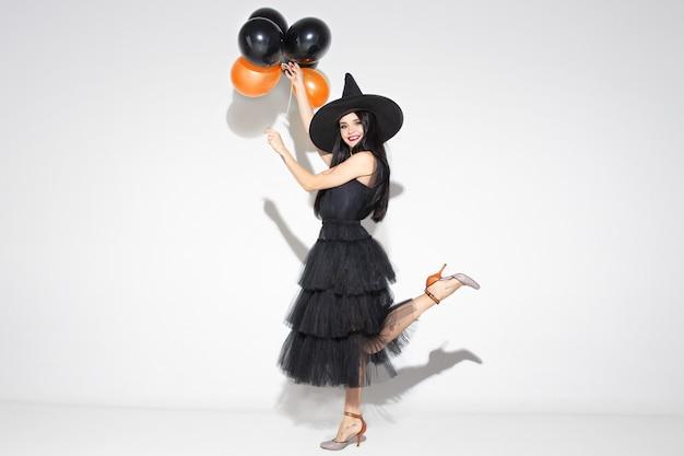 Giovane donna bruna in cappello nero e costume su sfondo bianco. modello femminile caucasico attraente. halloween, venerdì nero, cyber lunedì, vendite, concetto di autunno. copyspace. tiene palloncini, sorride.