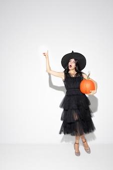 Giovane donna bruna in cappello nero e costume su sfondo bianco. modello femminile caucasico attraente. halloween, venerdì nero, cyber lunedì, vendite, concetto di autunno. copyspace. tiene a pompare, indicando.