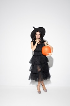 Giovane donna bruna in cappello nero e costume su sfondo bianco. modello femminile caucasico attraente. halloween, venerdì nero, cyber lunedì, vendite, concetto di autunno. copyspace. tiene la pompa.