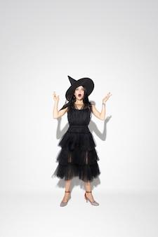 Giovane donna bruna in cappello nero e costume su sfondo bianco. modello femminile caucasico attraente. halloween, venerdì nero, cyber lunedì, vendite, concetto di autunno. copyspace. scioccato, stupito.