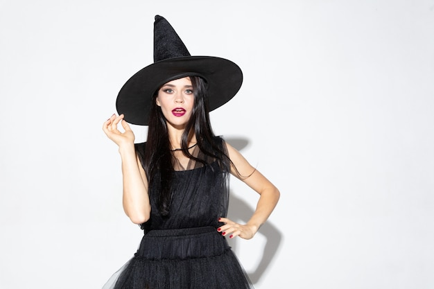 Young brunette woman in black hat and costume on white background. attractive caucasian female model. halloween, black friday, cyber monday, sales, autumn concept