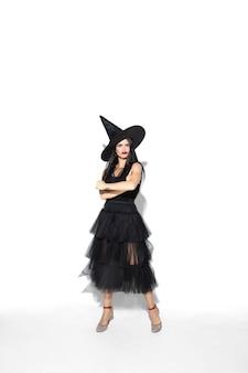 Giovane donna castana in cappello nero e costume su bianco