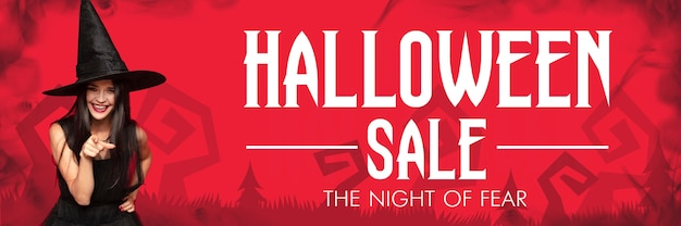 Young brunette woman in black hat on scary red background. attractive caucasian female model smiling. halloween sales, black friday, cyber monday, autumn concept. flyer for your ad. pointing up.