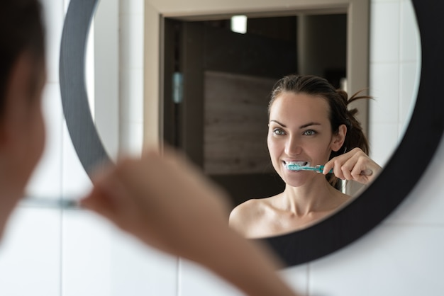 Young brunette woman brushing her teeth in front of bathroom mirror