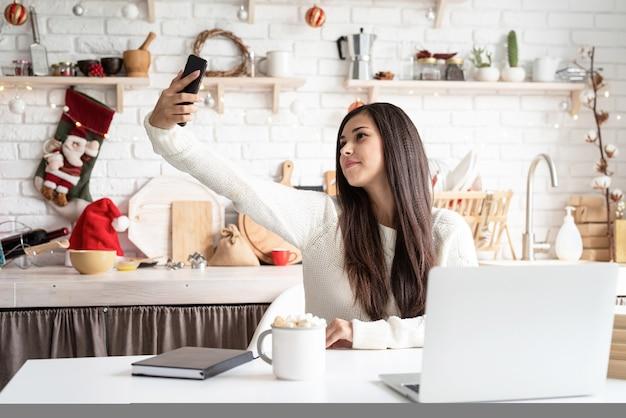 Молодая брюнетка женщина разговаривает с друзьями, используя свой мобильный телефон на кухне