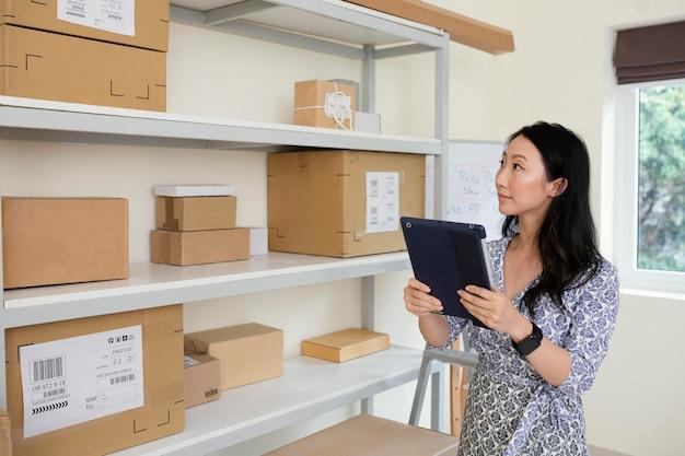 Giovane donna castana che controlla le informazioni sulla consegna dei pacchi