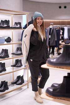 젊은 갈색 머리 여자는 상점에서 옷과 액세서리를 선택