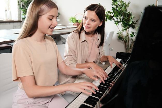 ピアノのそばに座って、家庭環境で一緒に遊んでいる間、彼女の賢い10代の娘に相談する若いブルネットの女性