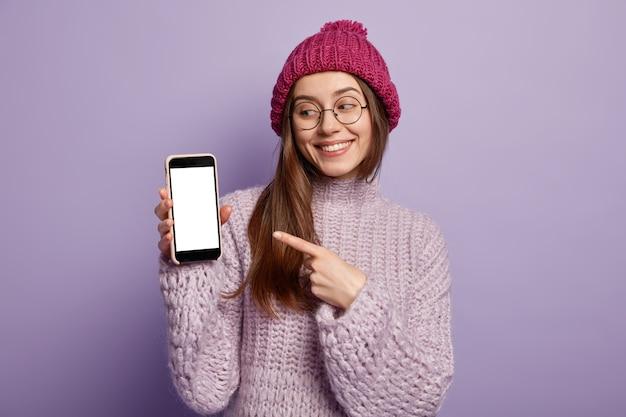 Giovane donna castana in vestiti di inverno accoglienti che tengono telefono