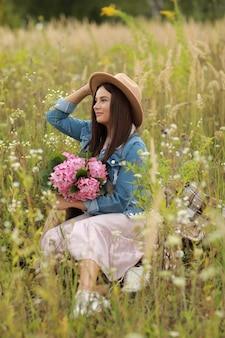 Young brunette woman in denim jacket, pink dress and hat holding bouquet of pink flowers