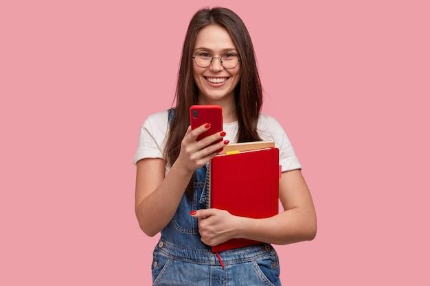 Giovane donna castana in tuta di jeans che tiene i blocchetti per appunti