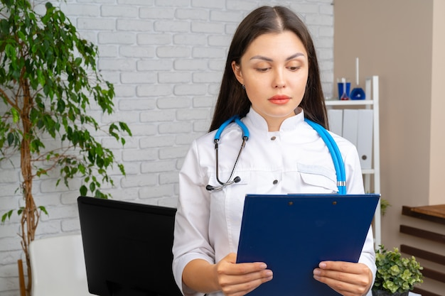 Young brunette woman doctor standing with clipboard in her office