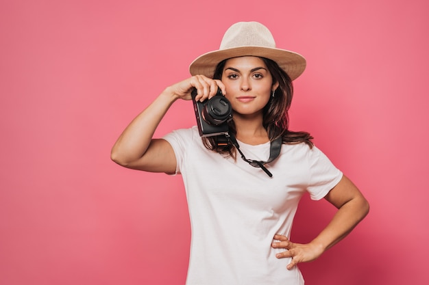Young brunette woman dressed in light t-shirt and straw hat, with a camera in her hand, thoughts about the future journey