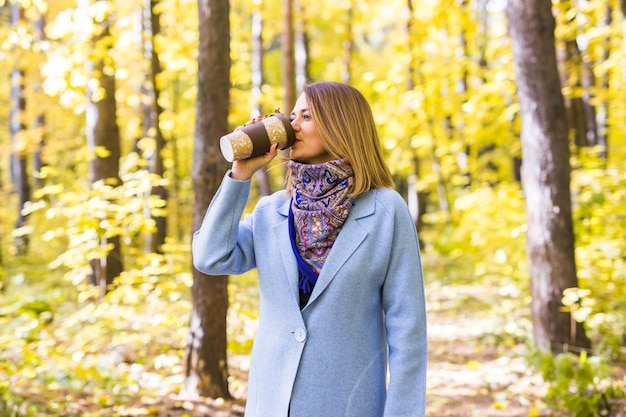 若いブルネットの女性は秋の公園でコーヒーを飲む