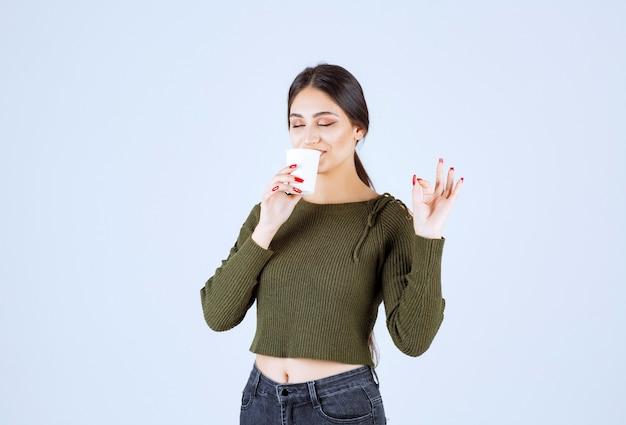 お茶のプラスチック カップを飲み、ok のサインを与える若いブルネットの女性。
