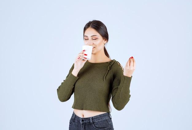 白い背景にお茶のプラスチック カップを飲む若いブルネットの女性。