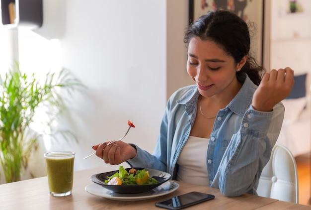 Молодая брюнетка ест салат в столовой, она пользуется телефоном