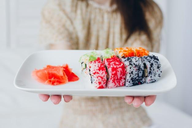 Молодая брюнетка ест суши