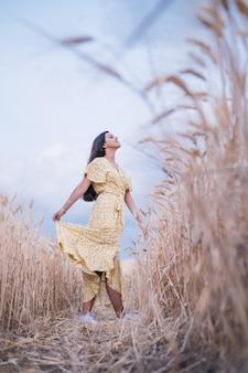 Молодая брюнетка женщина, наслаждаясь природой, стоя посреди пшеничного поля.