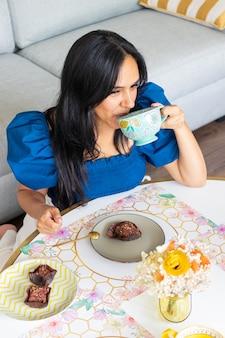 Молодая брюнетка любит есть сладости с кофе