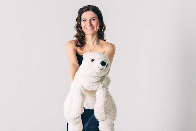 Young brunette woman in evening dress with polar bear toy