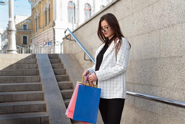 젊은 갈색 머리 여자 쇼핑 가방 및 구매를 검사합니다.