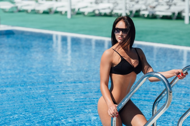Young brunette woman fitness model in black swimsuit and sunglasses poses in the pool