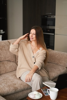 Young brunette woman freelancer at home on sofa working on laptop