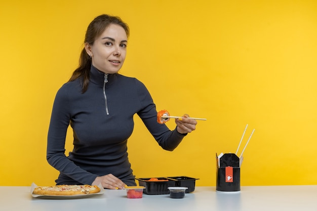 Young brunette woman girl in casual clothes hold in hand makizushi sushi roll served on black plate traditional japanese food isolated on yellow background studio portrait. people lifestyle concept