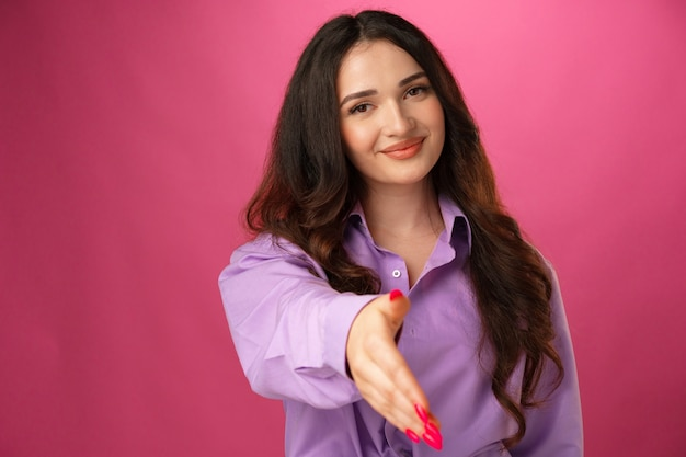 Young brunette woman giving hand for handshake against pink background