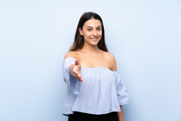 Young brunette woman handshaking after good deal