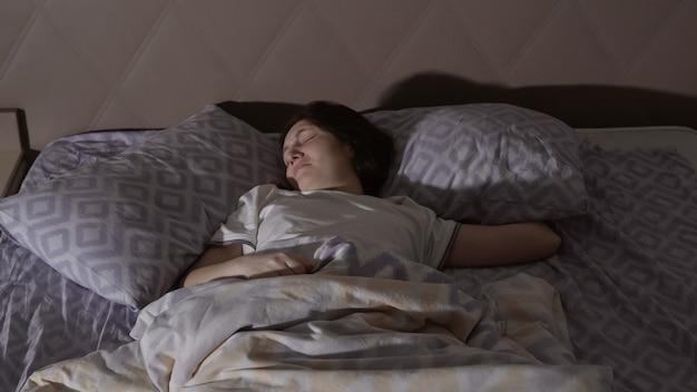 悪夢を持っている若いブルネットの女性。落ち着きのない夢。