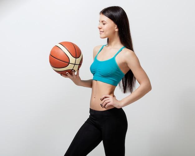 농구 공을 들고 젊은 갈색 머리 여자
