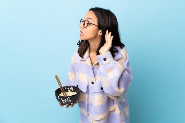耳に手を置くことで何かを聞いて分離された青に麺がいっぱい入ったボウルを保持している若いブルネットの女性