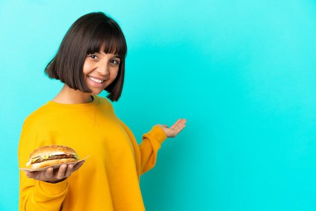 외진 배경 위에 햄버거를 들고 있는 젊은 브루네트 여성이 초대하기 위해 손을 옆으로 내밀고 있다