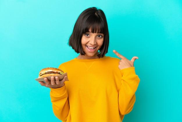 親指を立てるジェスチャーを与える孤立した背景の上にハンバーガーを保持している若いブルネットの女性
