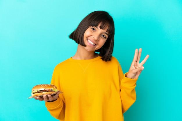 幸せな孤立した背景の上にハンバーガーを保持し、指で3を数える若いブルネットの女性