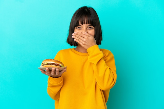 Молодая брюнетка женщина, держащая гамбургер на изолированном фоне, счастливая и улыбающаяся, прикрывая рот рукой