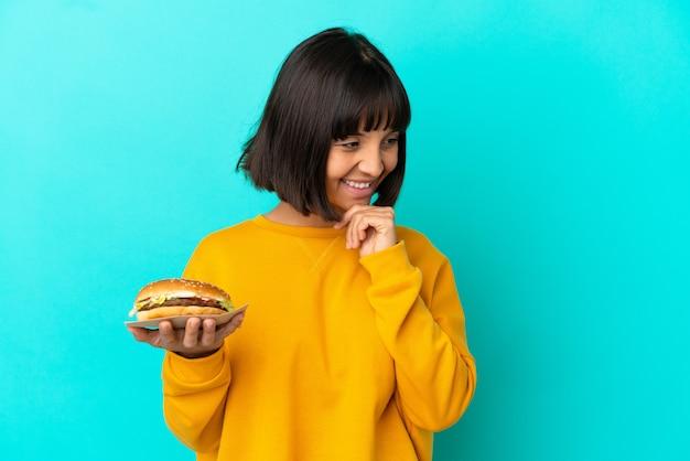 横を見て笑っている孤立した背景の上にハンバーガーを保持している若いブルネットの女性