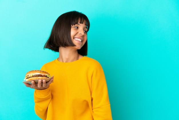 Молодая брюнетка женщина, держащая гамбургер на изолированном фоне, смотрит в сторону и улыбается