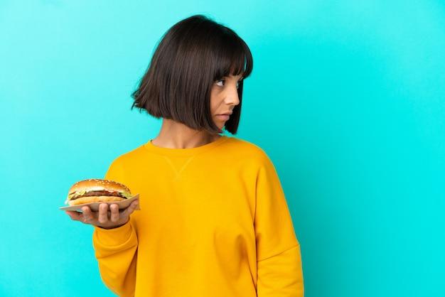 외진 배경 위에 햄버거를 들고 옆을 바라보는 젊은 브루네트 여성