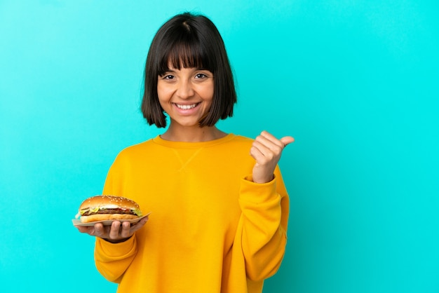 제품을 제시하기 위해 측면을 가리키는 외진 배경 위에 햄버거를 들고 있는 젊은 브루네트 여성